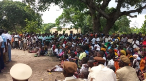 A crowd of villagers looks on, seated comfortably on grounds outside the Mayoral heart of the village in Nacala.